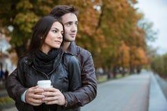 Paare mit dem Kaffee, der draußen weg schaut Lizenzfreie Stockfotografie