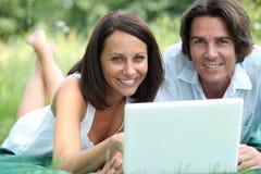 Paare mit dem Lügen im Gras Stockfoto