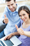 Paare mit dem Laptop, der sich Daumen zeigt Stockfotos