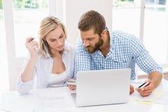 Paare mit dem Laptop und Handys, die auf Rechnungen sich besprechen Lizenzfreies Stockfoto