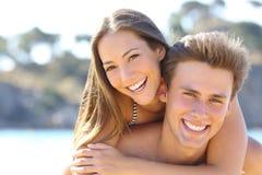 Paare mit dem perfekten Lächeln, das auf dem Strand aufwirft Stockbilder