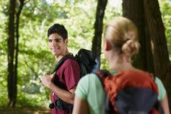 Paare mit dem Rucksack, der Trekking im Holz tut lizenzfreie stockfotos