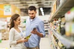 Paare mit dem Smartphone, der Olivenöl am Lebensmittelgeschäft kauft stockbild