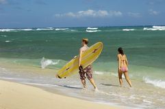 Paare mit dem Surfbrett, das auf den Strand geht Lizenzfreie Stockbilder