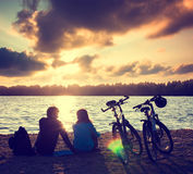 Paare mit den Fahrrädern, die bei Sonnenuntergang sich entspannen Lizenzfreie Stockfotos