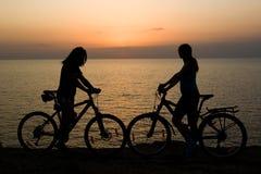 Paare mit den Fahrrädern, die Sonnenuntergang überwachen. Stockfotografie