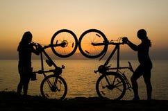 Paare mit den Fahrrädern, die Sonnenuntergang überwachen. Lizenzfreie Stockbilder