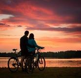 Paare mit den Fahrrädern, die Sonnenuntergang in Fluss aufpassen Stockfotos