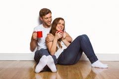 Paare mit den Kaffeetassen, die auf Boden sitzen Stockbild