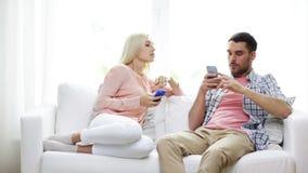 Paare mit den Smartphones, die zu Hause simsen stock video