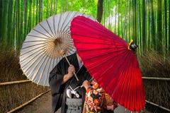 Paare mit den traditionellen japanischen Regenschirmen, die am Bambuswald in Arashiyama aufwerfen lizenzfreie stockfotos