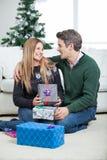 Paare mit den Weihnachtsgeschenken, die auf Boden sitzen Lizenzfreies Stockfoto