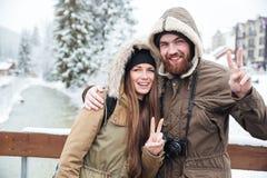 Paare mit der Fotokamera, die Frieden zeigt, gestikulieren auf Winterurlaubsort Lizenzfreie Stockfotografie