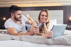 Paare mit der Kreditkarte und digitaler Tablette, die im Bett liegen und das on-line-Einkaufen tun lizenzfreie stockfotografie