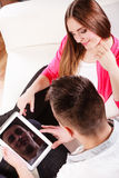 Paare mit der Tablette, die zu Hause auf Couch sitzt Lizenzfreies Stockfoto