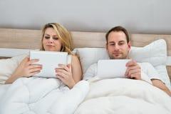 Paare mit digitalen Tabletten Stockbilder