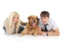 Paare mit einem Hund, der auf einem weißen Hintergrund liegt Lizenzfreies Stockbild