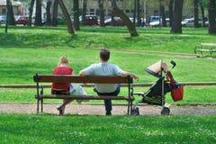 Paare mit einem Kinderwagen, der im Park stillsteht Stockbild