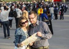 Paare mit einer Karte in einer gedrängten Stadt Lizenzfreies Stockbild