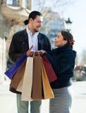 Paare mit Einkaufstaschen an der Straße Lizenzfreie Stockbilder