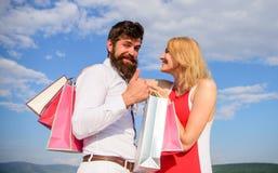 Paare mit Einkaufstaschen streicheln Hintergrund des blauen Himmels Mann mit Bart zeigt Daumen herauf Geste Jetzt zu kaufen Rat,  stockfoto