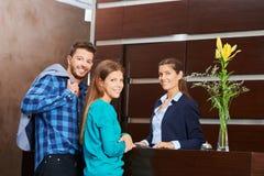 Paare mit Empfangsdame während der Hotelabfertigung stockfotos