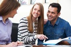 Paare mit Finanzberater-unterzeichnendem Dokument im Büro stockfotos