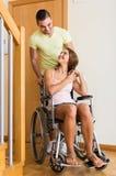 Paare mit Frau im Rollstuhl nahe Tür Lizenzfreie Stockfotos