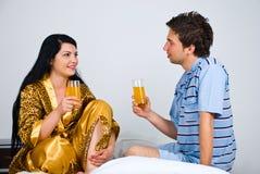 Paare mit frischem Orangensaft auf Bett im Morgen Stockfotos