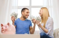 Paare mit Geld und piggybank ot verlegen zu Hause Lizenzfreie Stockbilder