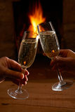 Paare mit Glas von Champagne Relaxing By Fire Stockfotos