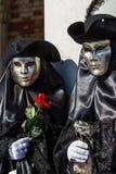 Paare mit goldener venetianischer Maske und schwarzes Kostüm mit Rot und Silberrosen während Venedig-Karnevals stockfotografie