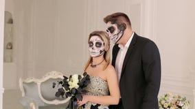 Paare mit Halloween-Schädelmake-up in einem Reinraum mit Weinleseinnenraum stock video footage