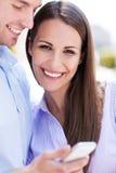 Paare mit Handy Lizenzfreie Stockfotos