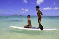 Paare mit ihrem Paddelvorstand lizenzfreie stockbilder