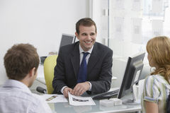 Paare mit Immobilienagentur In Office Stockbild