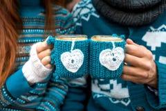 Paare mit Kaffeetassen im Winter lizenzfreie stockbilder