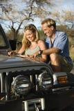 Paare mit Karte auf Auto-Haube Lizenzfreie Stockfotografie