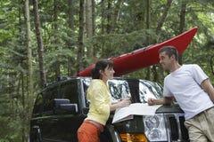 Paare mit Karte auf Auto-Mütze im Wald stockfoto