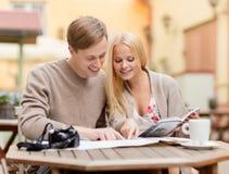 Paare mit Karten-, Kamera- und Reisendführer Lizenzfreie Stockfotografie
