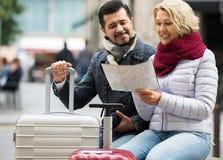 Paare mit Koffern, Kamera und Karte draußen Stockbilder