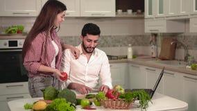 Paare mit Laptop während der Mahlzeit-Vorbereitung stock footage