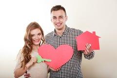 Paare mit Papierhaus und Herzen lieben Symbol Stockfotos