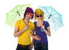 Paare mit Perücken, Sonnenbrille und Regenschirmen Stockfoto