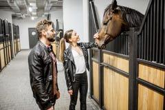 Paare mit Pferd im Stall lizenzfreies stockbild