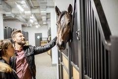 Paare mit Pferd im Stall lizenzfreie stockfotografie