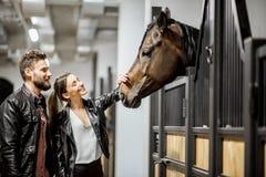 Paare mit Pferd im Stall lizenzfreies stockfoto