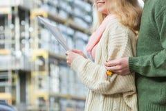 Paare mit Plan projektieren Schlüssel auf Baustelle Stockbilder