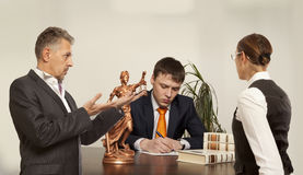 Paare mit Richterschreiben am Schreibtisch vor Gericht Lizenzfreies Stockbild