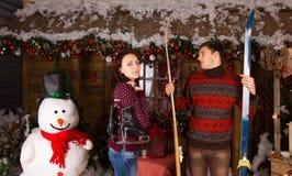 Paare mit Rochen und Skis vor Blockhaus Stockbilder